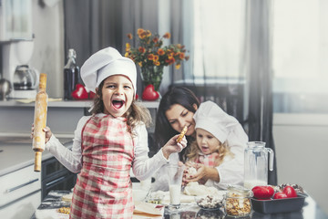 Little girl child with mother and sister happy cook at the table in the kitchen is lovely and beautiful