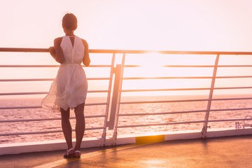 Wall Mural - Cruise ship vacation woman luxury travel watching sunset over ocean . Elegant lady in white dress on deck enjoying view of famous holiday destination. Girl on honeymoon getaway happy relaxing.