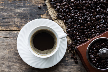 white coffee cup with Coffee beans On the old wooden background