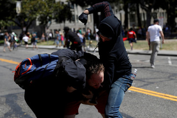 A photographer is being attacked by masked demonstrators in Martin Luther King Jr. Civic Center Park during a cancelled No Marxism in America rally and counter-protest in Berkeley