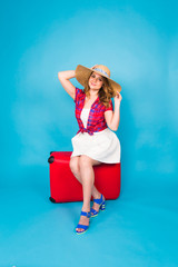 Young glamour woman with red suitcase. Travel, holidays and people concept