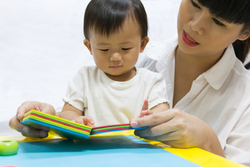 Asian adorable baby one year is looking book for kid.