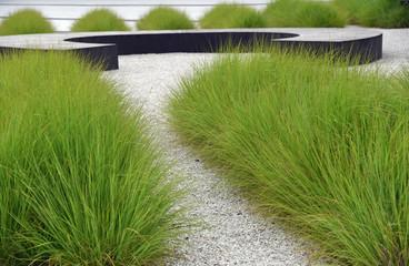Gepflegte Außenanlage mit Gras, Kies und einem runden Sitzelement