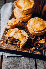 Fresh Traditional Australian meat mini pie on the wooden board on table background, closeup with copy space, top view, rustic style