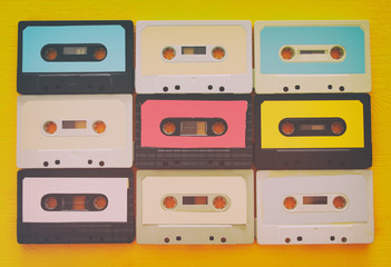 Retro cassette tape collection over yellow wooden table. top view. copy space