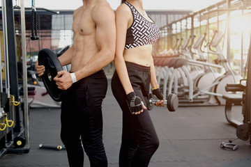 Athletic strong man and woman posing after fitness exercise in gym.