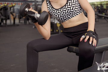 Fit woman wearing sports clothes weighing dumbbells in hands during workout in modern gym.