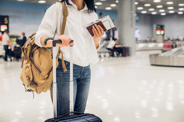 Woman backpacker holding passport and map with suitcase standing at check in baggage at airport terminal,traveler concept Wall mural
