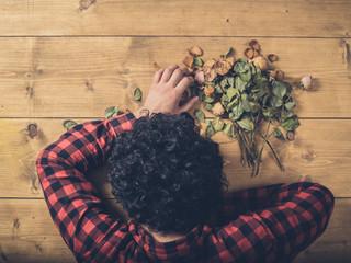 Sad man with dead flowers on the floor