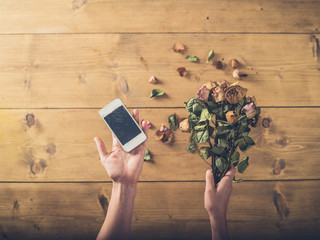 Woman with cracked smart phone and dead flowers