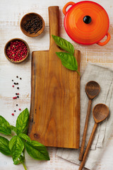 Black and red pepper, basil leaves,  ceramic pan,  wooden stand, simple old spoons and  linen napkin on light background. Kitchen accessories concept. Selective focus. Top view. Toned image.