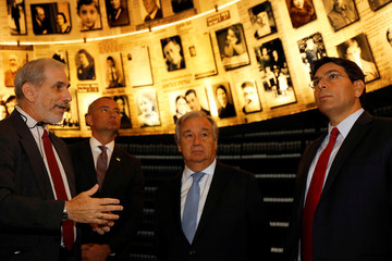 UN Secretary General Antonio Guterres is accompanied by Israel's Ambassador to the UN Danny Danon as they look at pictures of Jews killed in the Holocaust during a visit to the Hall of Names at Yad Vashem's Holocaust History Museum in Jerusalem