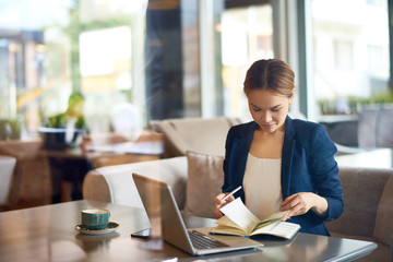 Confident young entrepreneur looking through notepad while preparing for important negotiations with business partner, interior of cozy cafe on background