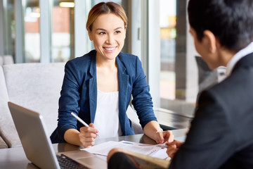 Attractive Asian entrepreneur discussing details of mutually beneficial cooperation with her female business partner while having negotiations at cozy cafe