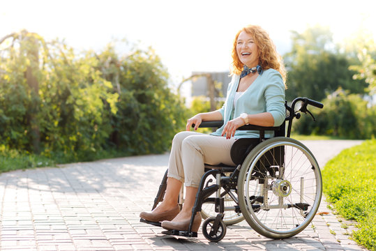 Chrerful wheelchaired woman laughing in the park