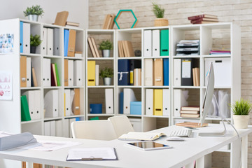 Interior of modern open plan office: documents, notepads and technologies located on desks, shelves with colorful folders, no people