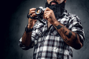 Bearded photographer holds compact DSLR camera over grey background.