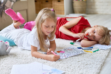 Portrait of two little girls drawing coloring pictures together lying on floor in cozy living room at home