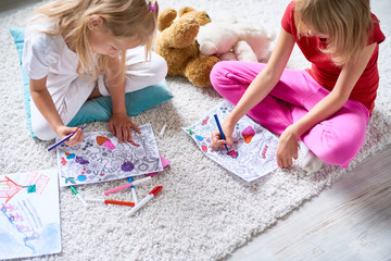 High angle portrait of two little sisters coloring pictures together sitting on thick carpet at home in cozy living room