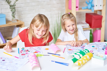 Portrait of two laughing little girls enjoying art class siting at desk and coloring pictures together