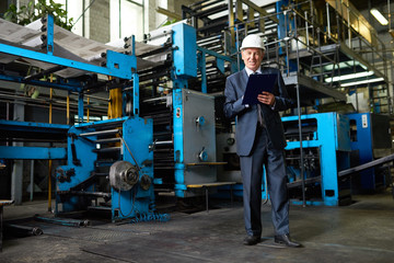 Portrait of senior businessman  wearing hardhat on tour in modern factory looking at camera and smiling holding clipboard