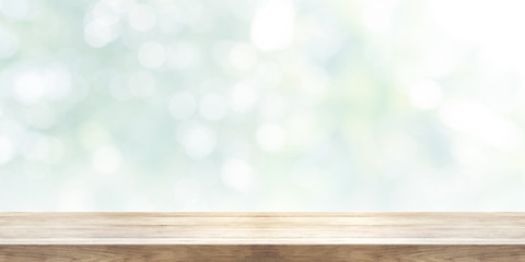 Empty wooden table top with blurred abstract background. Panoramic banner.