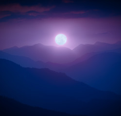 Rising of the full moon above the mountain valley