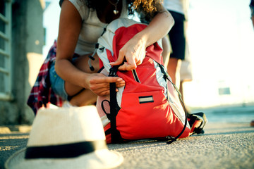 Young tourist girl is packing her backpack and hat.