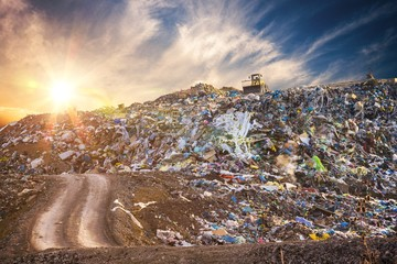 Pollution concept. Garbage pile in trash dump or landfill at sunset.