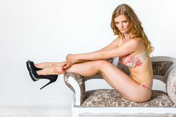 Sexy girl in underwear and black shoes is sitting on the sofa