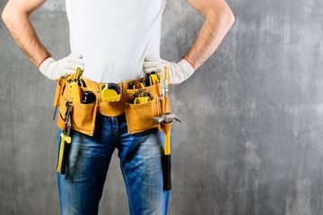 unknown handyman with hands on waist and tool belt with construction tools against grey background with copyspace for text. DIY tools and manual work concept