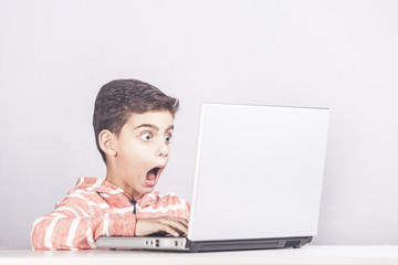 Little boy reacts after accidentally watching inappropriate content while surfing the internet. Internet safety and parental control concept
