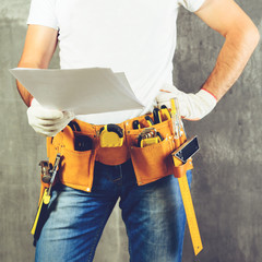 unknown handyman with hand on waist and tool belt with construction tools holding the project plane against grey background, toned image. DIY tools and manual work concept