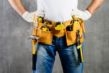 unknown handyman with hands on waist and tool belt with construction tools against grey background. DIY tools and manual work concept