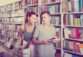 portrait of  teenage boy and girl customers looking at open book