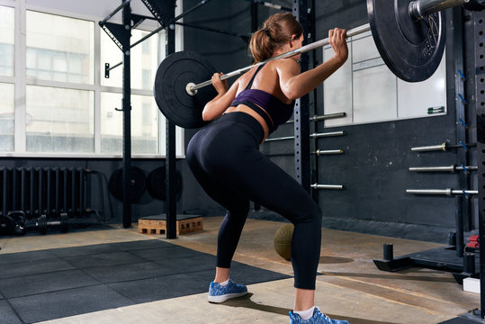 Back view of  strong young woman lifting heavy barbell performing shoulder squat during intense workout in modern gym