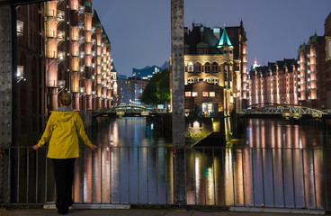 long exposure of young woman in yellow raincoat standing on bridge in illuminated old warehouse district Speicherstadt in Hamburg, Germany at night