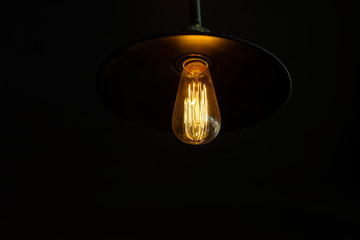 Retro light bulb hanging with dark space background for your decoration, concept of creativity
