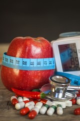 Red apple with measuring tape to measure length. Treatment of obesity and diabetes, measurement of blood pressure.