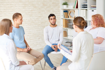 Group of young people sitting in circle sharing mental problems with female psychiatrist holding clipboard