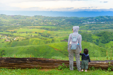 Happy mother holding daughter hands relax with blue sky and mountain landscape. Adventure travel of parent and kid.