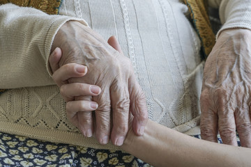 wrinkled hand holding a younger hand