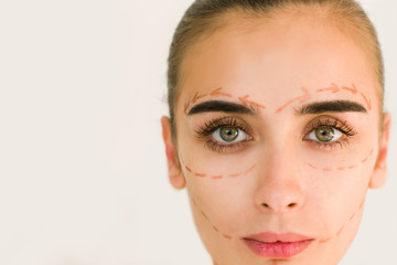 Beautiful girl with dark eyebrows with perforation lines on face, plastic surgery concept, close up portrait. Look at the camera.
