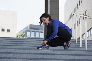 Woman tying shoe lace on staircase