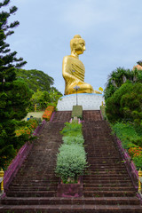 Stairs to Golden big Buddha statue on top of a hill. As a tourist destination, and how Buddhist place of worship.