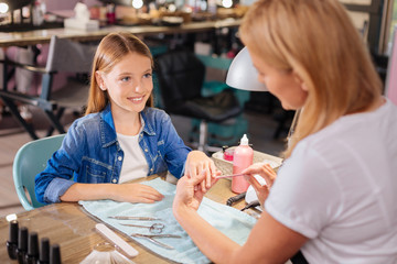 Young manicurist filing little finger nail of a teenage girl
