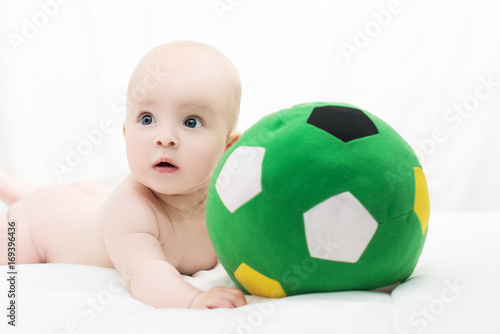 baby boy or girl lying down on his belly and playing with