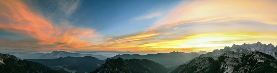 Wall Mural - Mountain landscape at sunset in Julian Alps. Amazing view on colorful clouds and layered mountains.