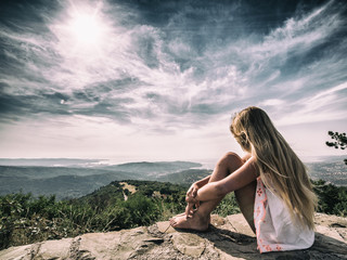 Girl sitting in front of dramatic landscape