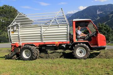 Landwirt Bergbauer Bauer sitzt in einer Erntemaschine Ladewagen